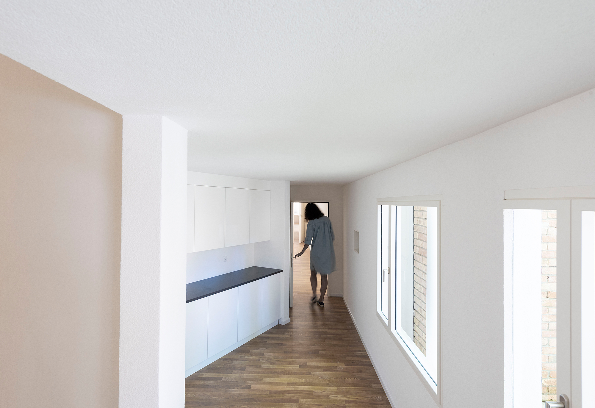 Interior view of the project with disproportionately sized doors, rooms and windows. A woman goes through a door that is obviously too small.