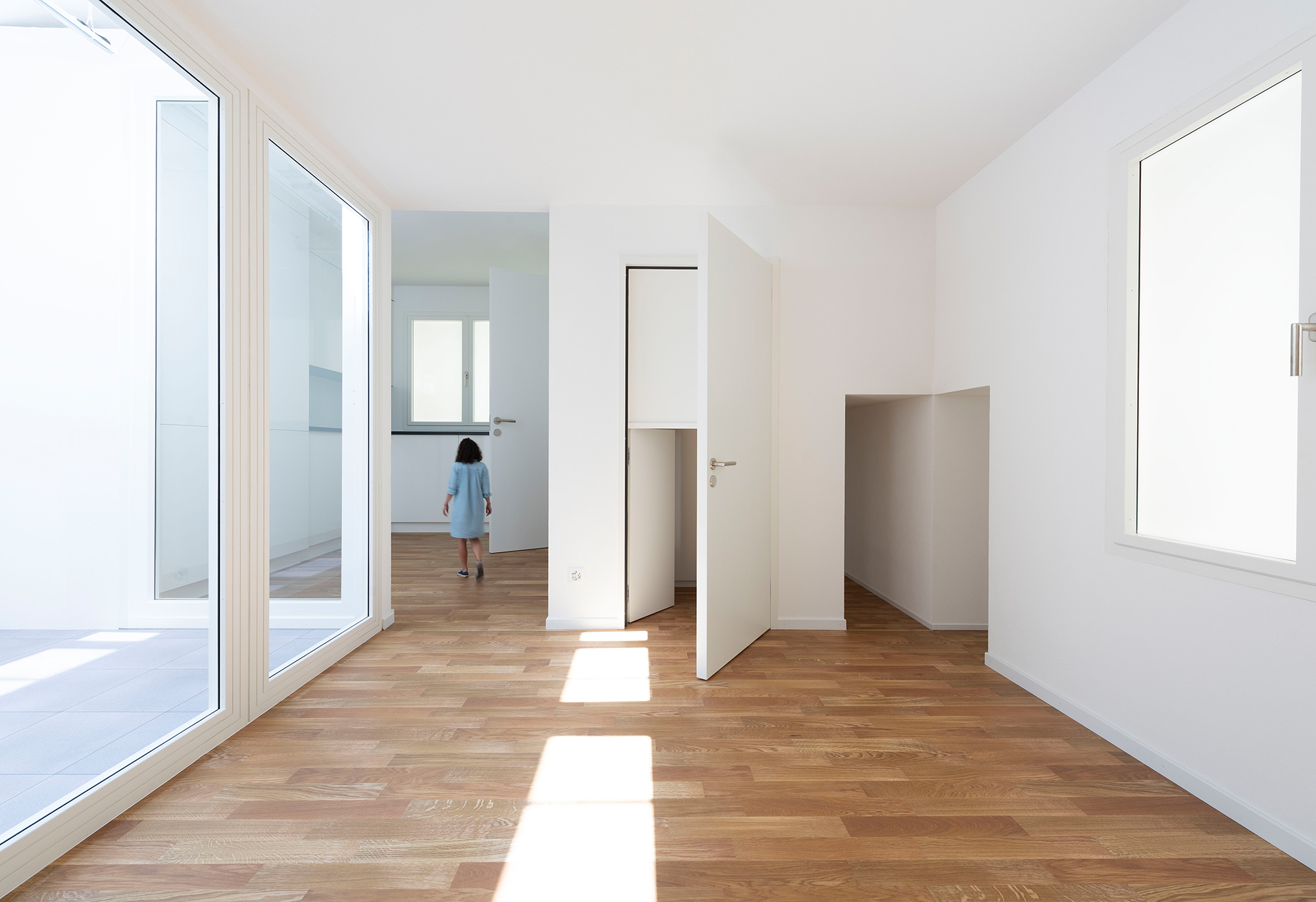 Interior view of the project with disproportionately sized doors, rooms and windows. A woman walks around an oversized room.