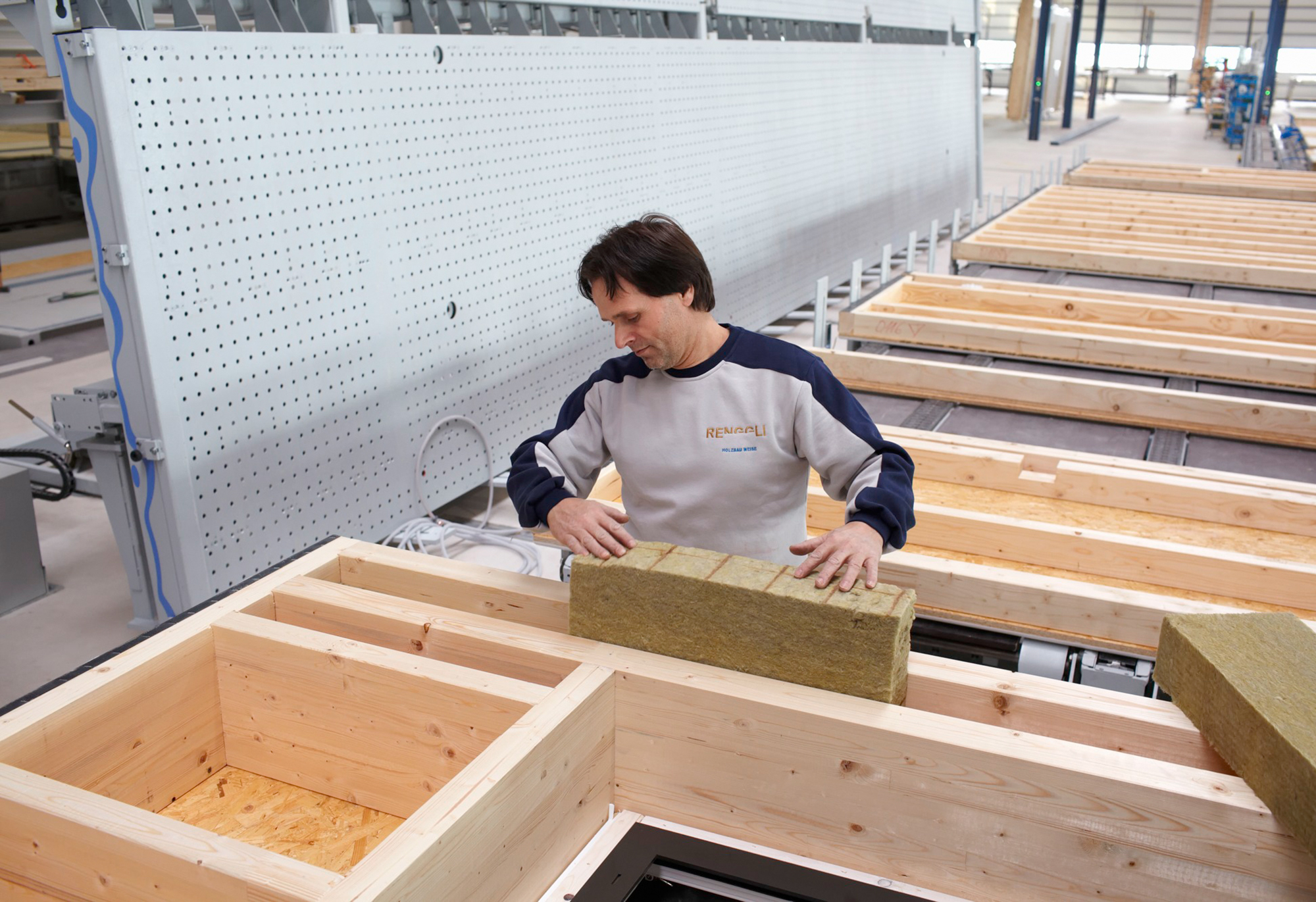 A worker is placing insulation material into the timber building elements in the Renggli factory