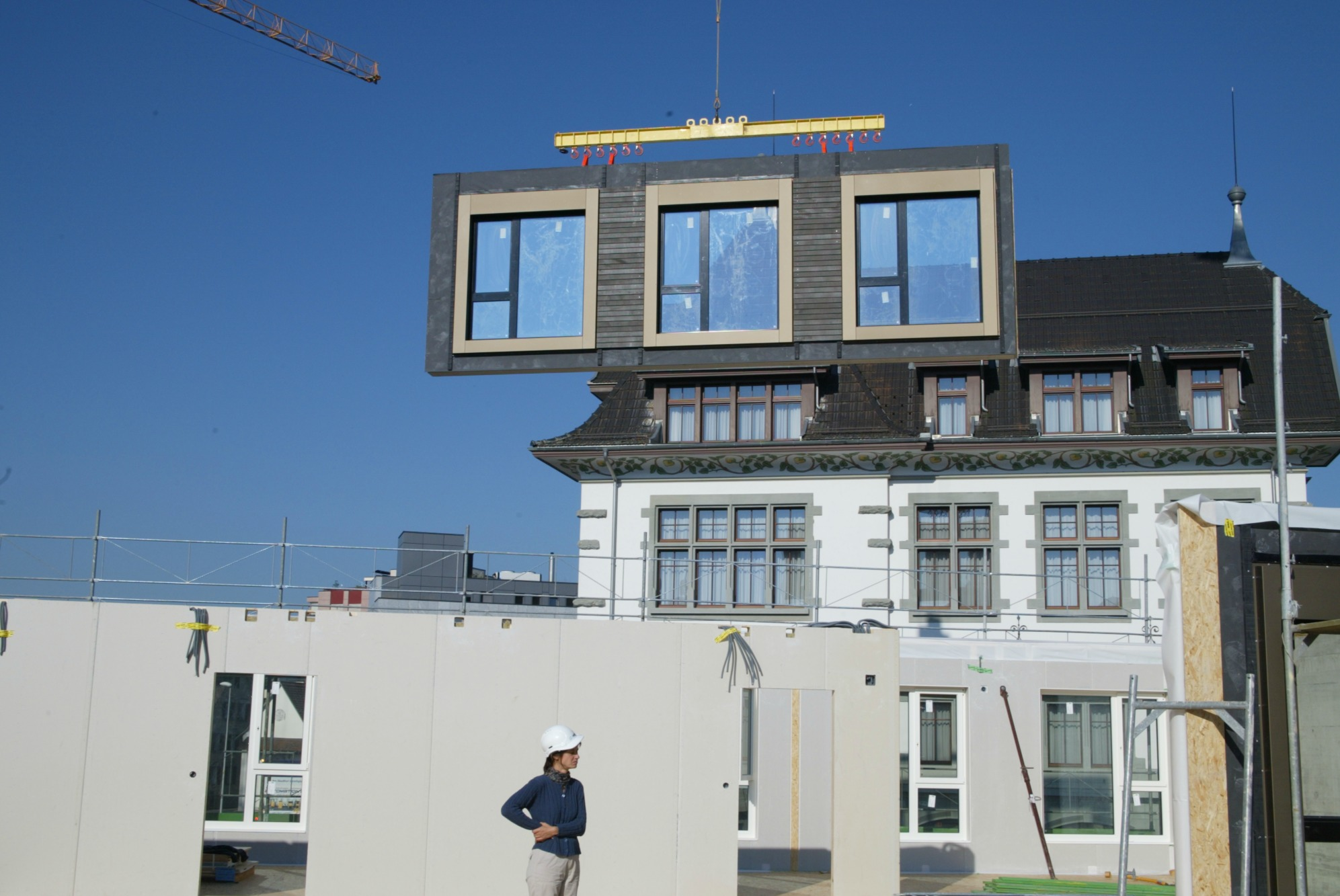 An exterior wall element with three built-in windows and facades hangs on a crane.